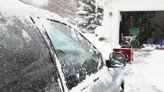 Car Covered In Snow Parked On A Snowy Driveway With Garage Door Opened