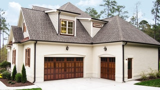 Cottage style home with brown wood garage doors